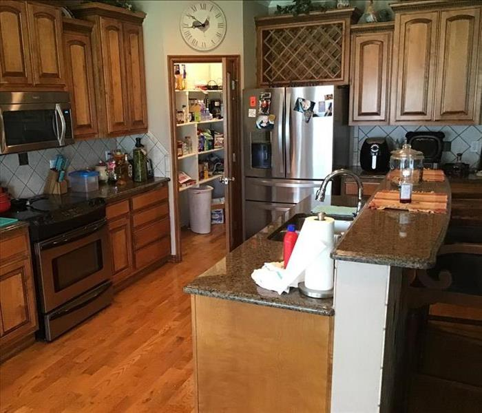 kitchen cabinets and wood floors flooded with water