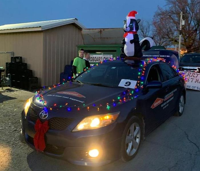 Eric at the Salina Christmas Parade with our mascot Lilly on the roof. Some of our candy throwers in the backgrond.